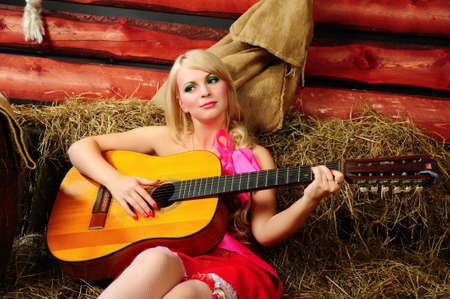 The blonde with a guitar on a mow  版權商用圖片