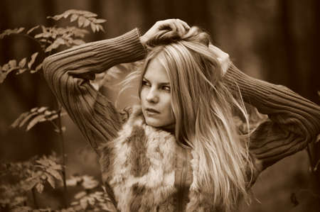sepia toned: beautiful young blond woman in autumn park