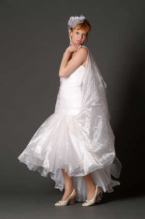 woman in a wedding dress on a gray background photo