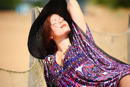young woman in a wide-brimmed hat on the beach Stock Photo - 10829679