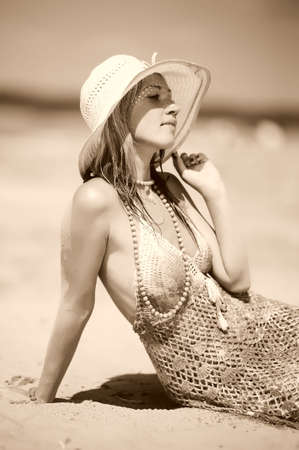 Beautiful young blonde girl in hat on the beach photo