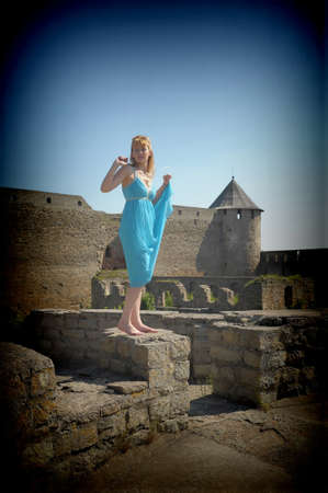 the girl in a blue dress on walls of a medieval fortress photo