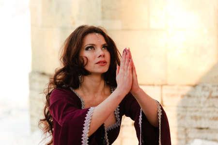 pentimento: La ragazza in un abito medievale prega