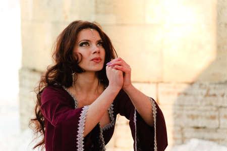 abito medievale: La ragazza in un abito medievale prega