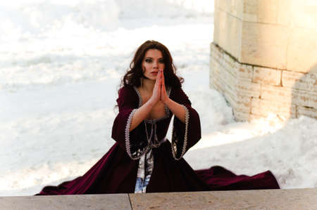 the girl in a medieval dress prays Stock Photo - 13253059