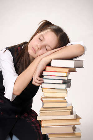 girl sleeping on a pile of textbooks photo