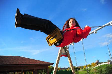 Girl swinging on a swing photo