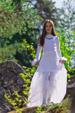 space age: girl in white dress in the woods Stock Photo