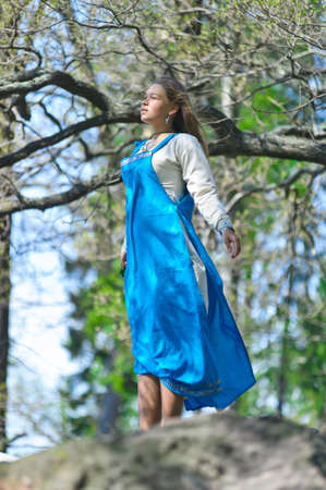 long tail: the girl in a blue medieval sundress standing on the rock and looking in a distance Stock Photo