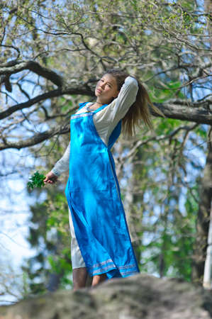 the girl in a blue medieval sundress standing on the rock and looking in a distance Stock Photo - 13384171