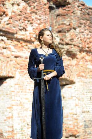 middeleeuwse jurk: Jong meisje in middeleeuwse jurk met zwaard Stockfoto