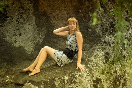 beautiful young woman on the rocks photo