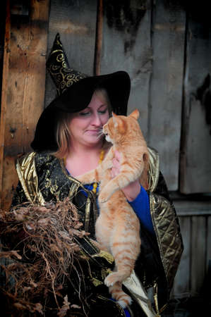 wicca: Witch with a red cat in her arms Stock Photo