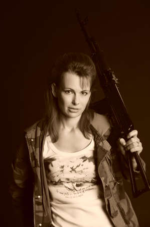 chica: beautiful young woman with a gun Stock Photo