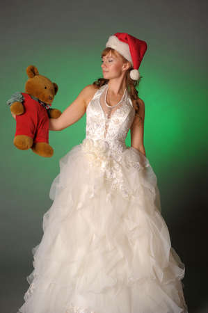 Bride in a Christmas hat with teddy bear photo