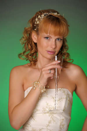 the bride with a glass of champagne in the studio photo