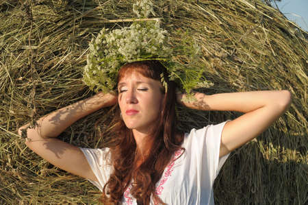 girl in a haystack in a wreath photo