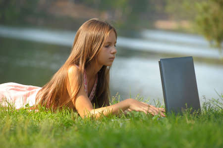girl with a laptop by the lake photo