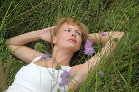 young woman lying in a meadow of grass and flowers photo