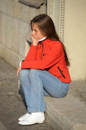 verdrietig meisje: Sad girl zittend op de deur Stockfoto