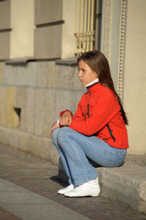 sad girl sitting on the doorstep photo