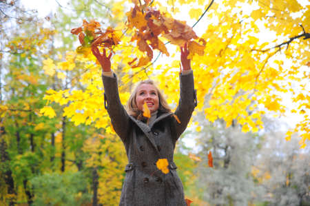 Girl throwing leaves Stock Photo - 10564193