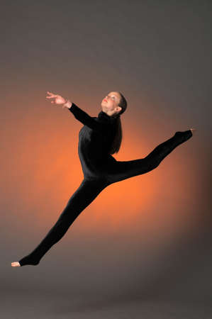 Gymnast jumping in the studio in a black suit photo