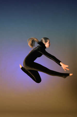 Gymnast jumping in the studio in a black suit Stock Photo - 10728224