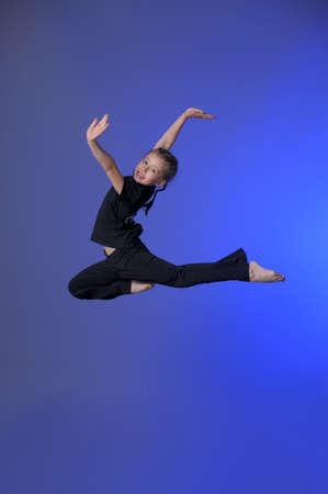 Gymnast girl jumping studio photo