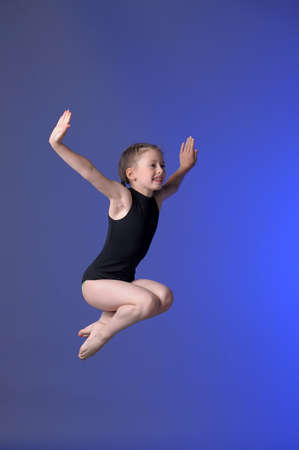 Gymnast girl jumping studio photo