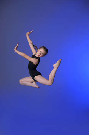 leap: Gymnast girl jumping studio Stock Photo
