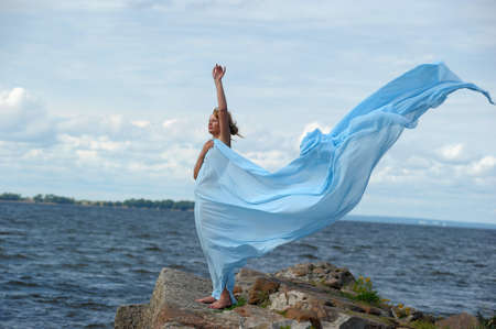 young woman standing on a promontory and enjoying the wind Stock Photo - 10727316