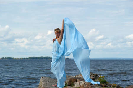 young woman standing on a promontory and enjoying the wind Stock Photo - 10727320