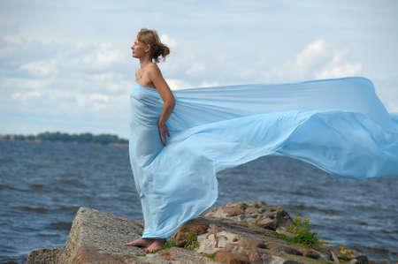 scarf beach: mujer joven de pie en un promontorio y disfrutando del viento Foto de archivo