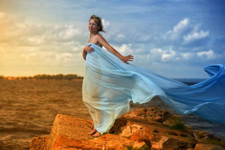 transparent dress: young woman standing on a promontory and enjoying the wind