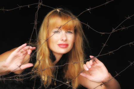 keepout: a woman with a barbed wire fence in the hands