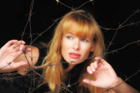 a woman with a barbed wire fence in the hands  photo