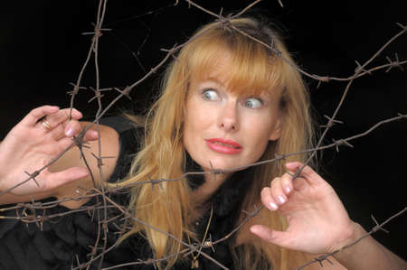 lock out: a woman with a barbed wire fence in the hands