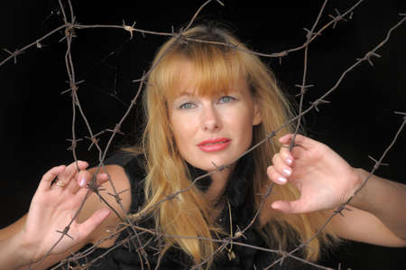 a woman with a barbed wire fence in the hands  Stock Photo - 10727464