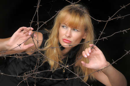 a woman with a barbed wire fence in the hands Stock Photo - 10727466