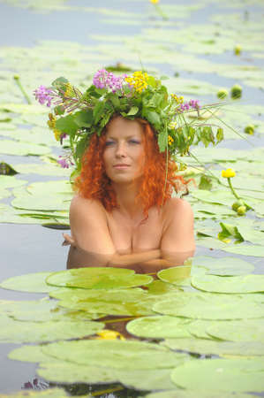 mermaid in the water with a wreath on head photo