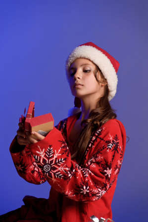 Girl teenager in santa hat with Christmas gifts Stock Photo