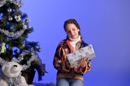 teen girl next to a Christmas tree with gifts photo