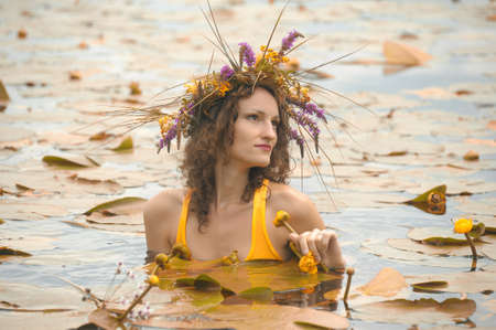 sirena in acqua con una corona di fiori sulla testa