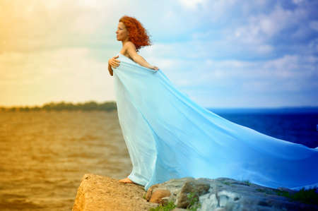 young woman standing on a promontory and enjoying the wind Stock Photo - 10778475