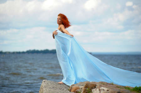 young woman standing on a promontory and enjoying the wind photo