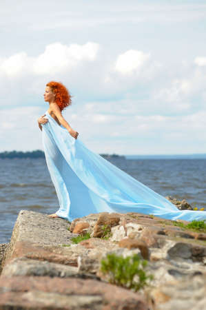 young woman standing on a promontory and enjoying the wind Stock Photo - 10778472