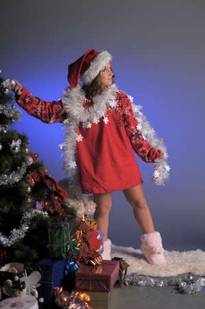 Young girl as Santa Claus decorating Christmas tree  photo