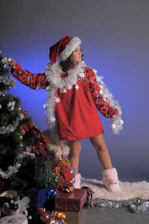 Young girl as Santa Claus decorating Christmas tree  photo