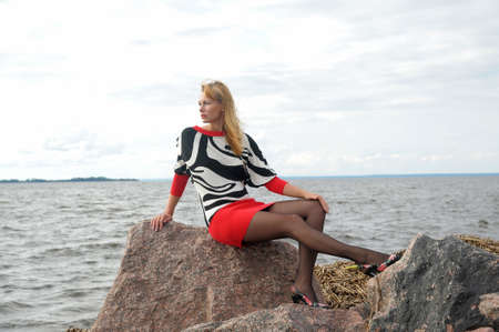 girl sitting on a rock on the shore of the Sea photo